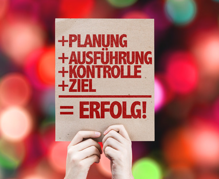 execution: Hands holding cardboard on bokeh background with text: Planning   Execution   Control   Target = Success (in German) Stock Photo
