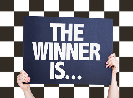 checkered background: Hands holding cardboard on checkered background with text: The winner is ...