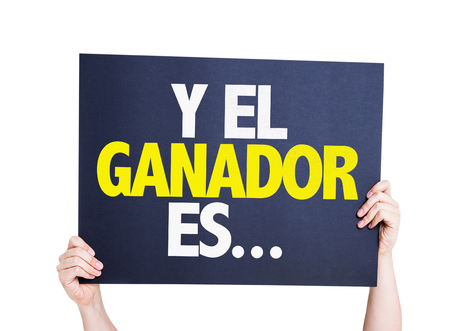 medalist: Hands holding cardboard on white background with text: Y el ganador es ... (and the winner is ... in Spanish)
