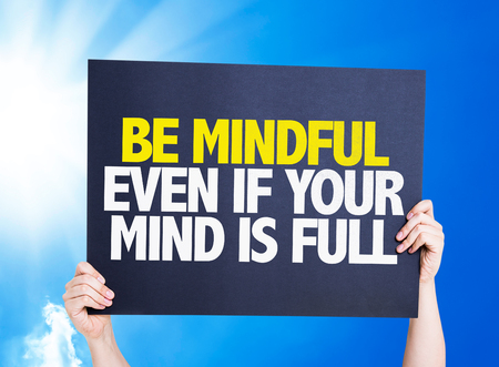mindful: Hands holding cardboard on sky background with text: Be mindful even if your mind is full Stock Photo