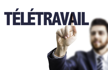 teleworker: Business man pointing to transparent board with text: Teletravail (teleworking in French)