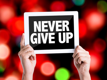 Hands holding tablet pc on bokeh background with text: Never give up Stock Photo