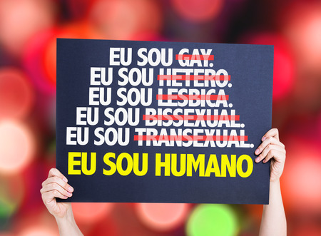 Hands holding cardboard on bokeh background with text: Eu sou humano (I am human in Portuguese)