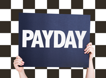 checkered background: Hands holding cardboard on checkered background with text: Payday