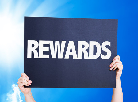 attainment: Hands holding cardboard on sky background with text: Rewards Stock Photo