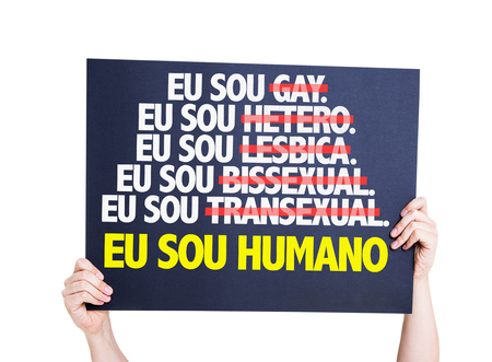sou: Hands holding cardboard on white background with text: Eu sou humano (I am human in Portuguese) Stock Photo