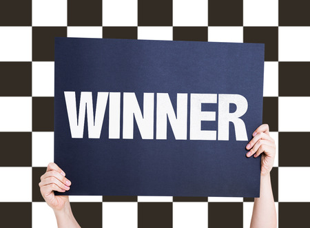 checkered background: Hands holding cardboard on checkered background with text: Winner Stock Photo