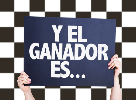 checkered background: Hands holding cardboard on checkered background with text: Y el ganador es ...(and the winner is ... in Spanish) Stock Photo