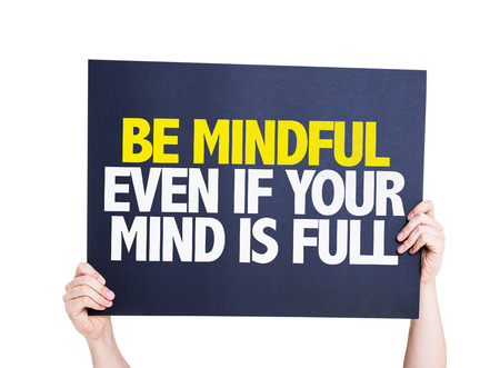 Hands holding cardboard on white background with text: Be mindful even if your mind is full