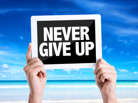 Hands holding tablet pc on beach background with text: Never give up Stock Photo