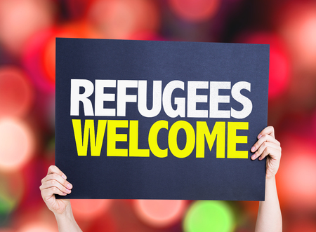 Hands holding cardboard on bokeh background with text: Refugees welcome