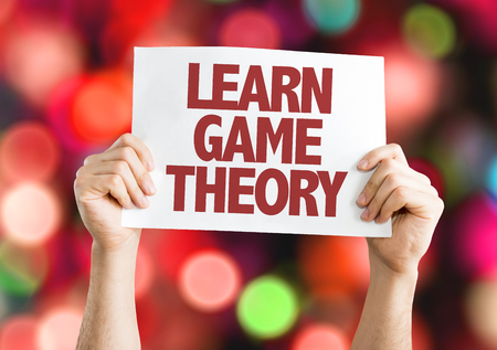 Hands holding cardboard on bokeh background with text: Learn game theory Stock Photo