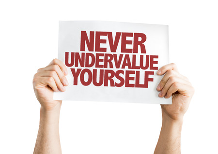 self worth: Hands holding cardboard on white background with text: Never undervalue yourself