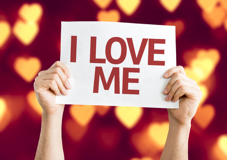 Hands holding cardboard on heart bokeh background with text: I love me Stock Photo