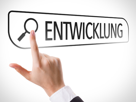 url virtual: Hand searching online on white background with text: Entwicklung (development in German) Stock Photo