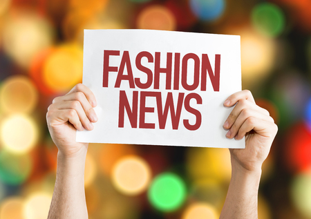 Hands holding cardboard on bokeh background with text: Fashion news Stock Photo
