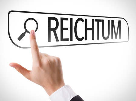 url virtual: Hand searching online on white background with text: Reichtum (wealth in German)