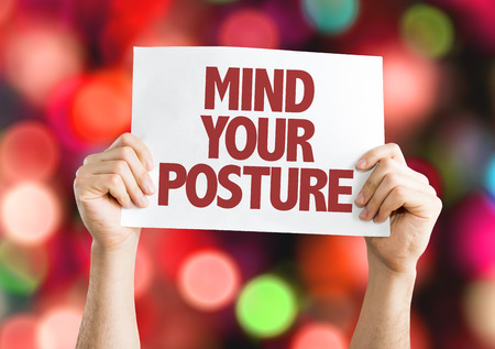 Hands holding cardboard on bokeh background with text: Mind your posture Stock Photo