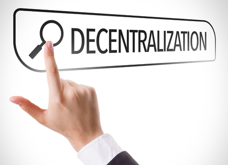 diverge: Hand searching online on white background with text: Decentralization Stock Photo