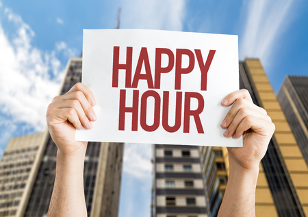 hands  hour: Hands holding cardboard on city background with text: Happy hour Stock Photo