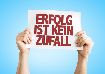 Hands holding cardboard on blue background with text: Erfolg ist kein zufall (success is no accident in German) Stock Photo