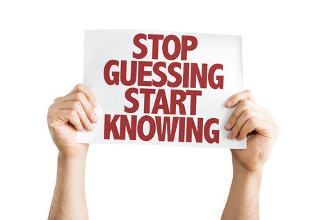 guessing: Hands holding cardboard on white background with text: Stop guessing start knowing Stock Photo
