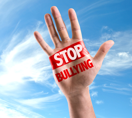 Hand on sky background with text: Stop bullying