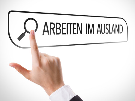 url virtual: Hand searching online on white background with text: Arbeiten im ausland (working abroad in German) Stock Photo