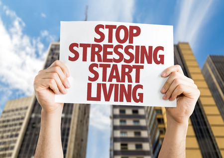 stressing: Hands holding cardboard on city background with text: Stop stressing start living