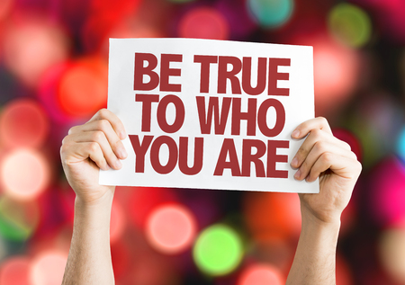 Hands holding cardboard on bokeh background with text: Be true to who you are Stock Photo