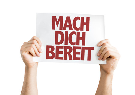 mach: Hands holding cardboard on white background with text: Mach dich bereit (get ready in German)