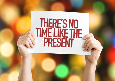 no time: Hands holding cardboard on bokeh background with text: Theres no time like the present