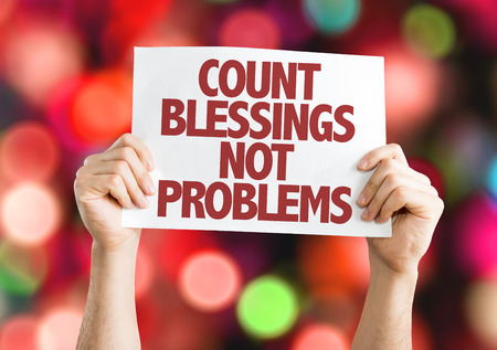 blessings: Hands holding cardboard on bokeh background with text: Count blessings not problems
