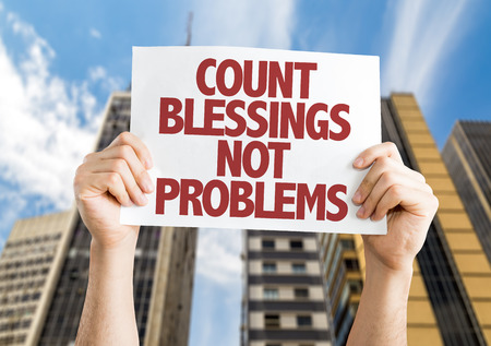blessings: Hands holding cardboard on city background with text: Count blessings not problems Stock Photo