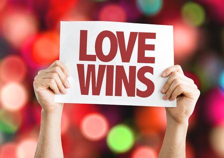 Handen die karton op bokeh achtergrond met tekst houden: Liefde wint Stockfoto - 64277031