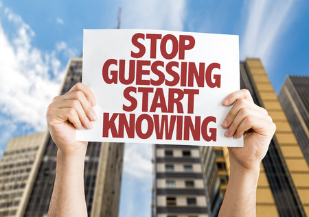 guessing: Hands holding cardboard on city background with text: Stop guessing start knowing
