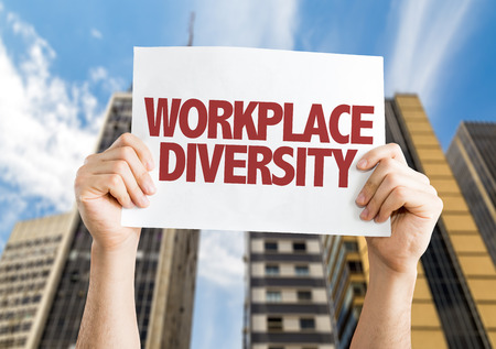 competitividad: Hands holding cardboard on city background with text: Workplace diversity