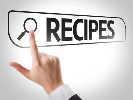 url virtual: Hand searching online on white background with text: Recipes Stock Photo