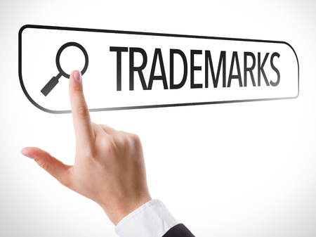 Hand searching online on white background with text: Trademarks