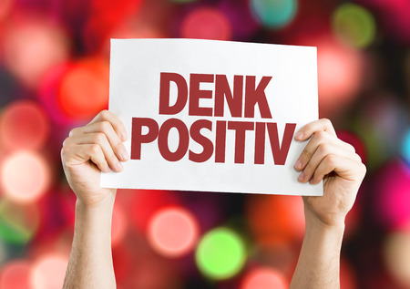 positiv: Hands holding cardboard on bokeh background with text: Denk positiv (think positive in German) Stock Photo