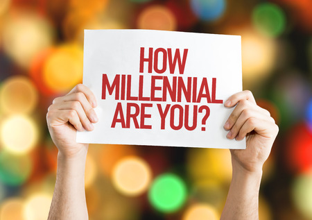 identidad cultural: Hands holding cardboard on bokeh background with text: How millennial are you? Foto de archivo