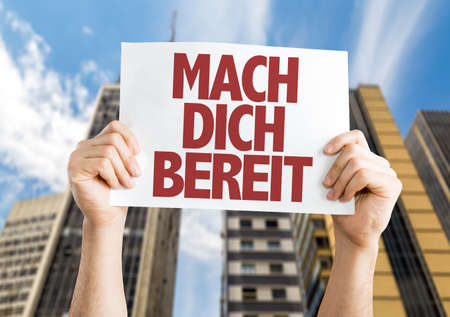 get ready: Hands holding placard with Get Ready in German on city background