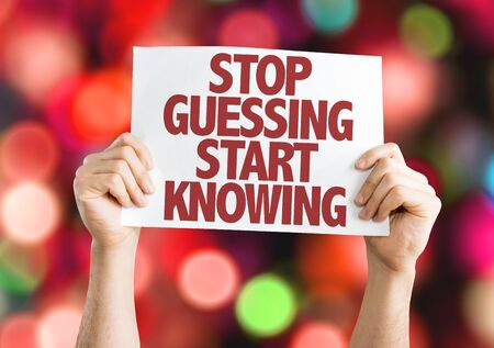 Hands holding placard with Stop Guessing Start Knowing on bokeh background