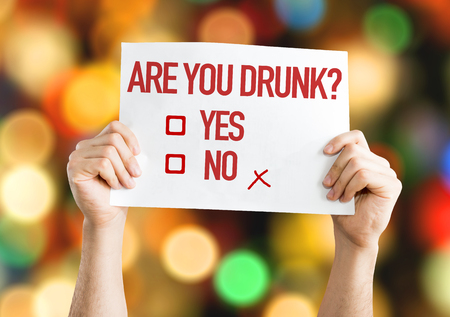 sober: Hands holding placard with Are You Drunk on bokeh background Stock Photo