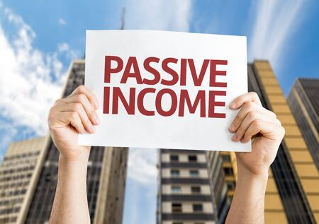 passive earnings: Hands holding placard with Passive Income on city background