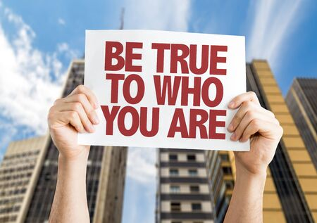 self worth: Hands holding placard with Be True To Who You Are on city background