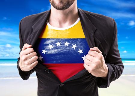 Businessman stretching suit with Venezuela flag on beach background Stock Photo