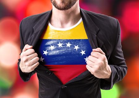 bandera de venezuela: El hombre de negocios se extiende traje con la bandera de Venezuela en el fondo del bokeh Foto de archivo