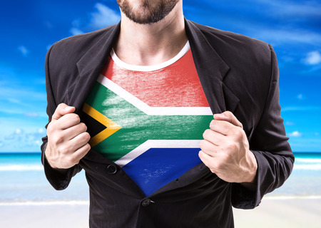 south africa flag: Businessman stretching suit with South Africa flag on beach background