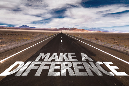 Make a difference written on the road Foto de archivo